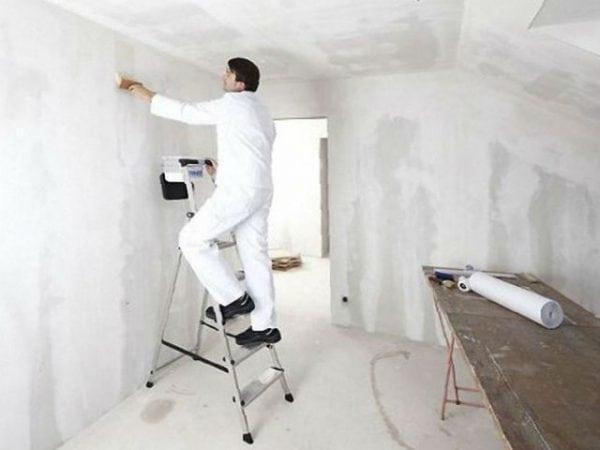 Мужчина делает ремонт в комнате