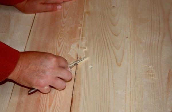 Мужчина шпаклюет деревянный пол