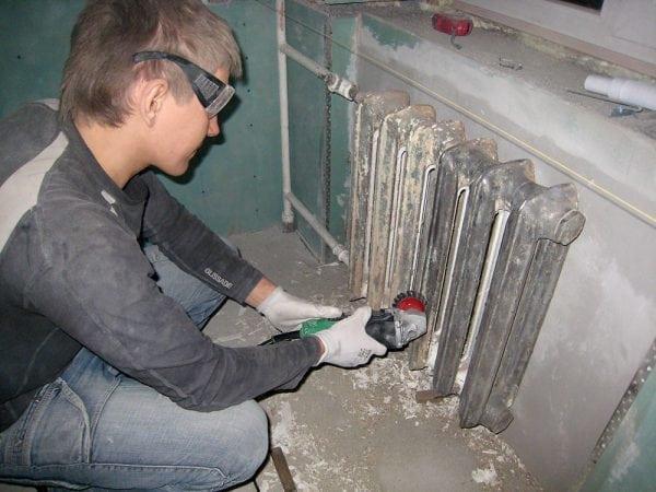 Мужчина снимает с металла старую краску