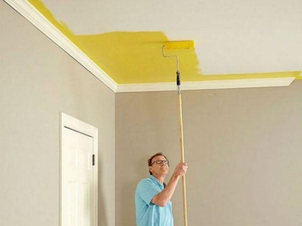 Мужчина красит потолок водоэмульсионной краской