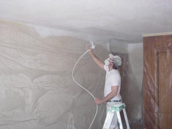 Процесс нанесения краски на потолок краскопультом