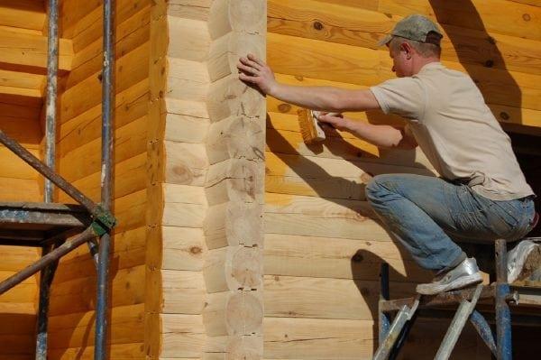 Процесс окрашивания стены деревянного дома