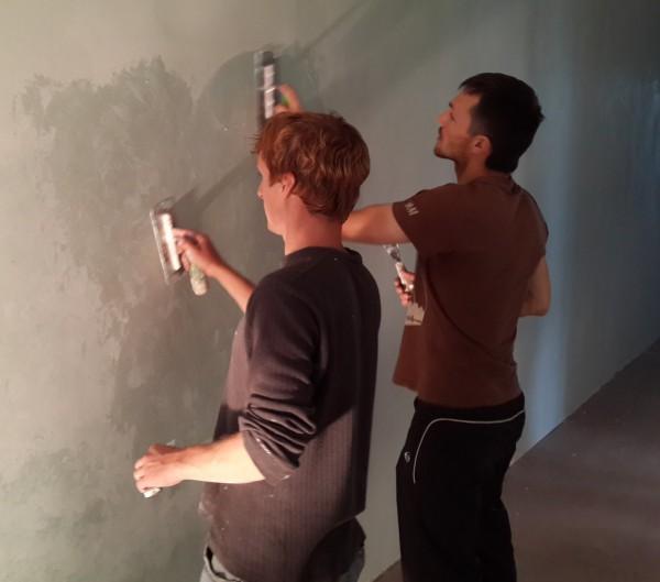 На стену наносят декоративную краску