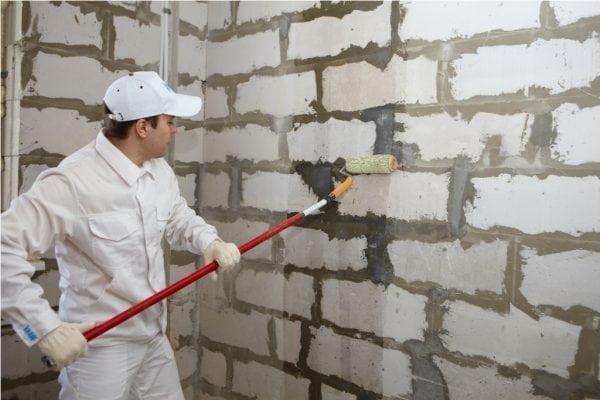 Нанесение грунтовки глубокого проникновения на стену из блоков
