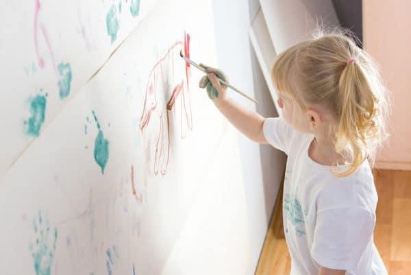 Девочка рисует на обоях