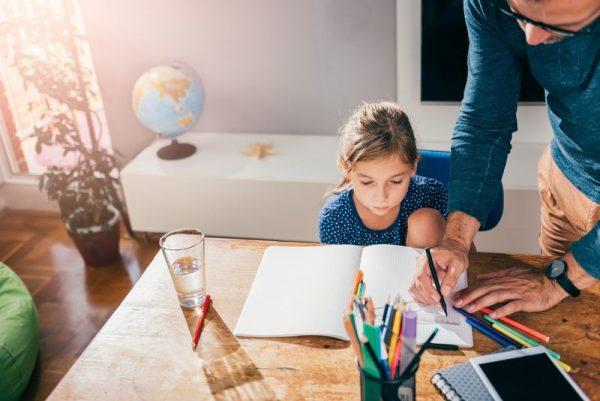 Девочка в своей комнате делает уроки