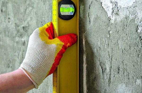 Проверка ровности стены при помощи уровня или отвеса вертикально