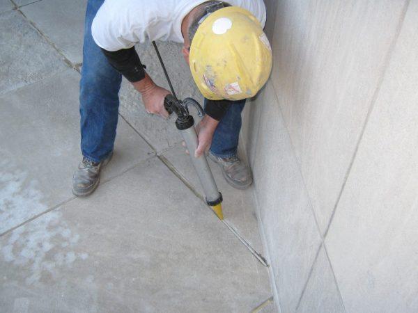 Заполнение стыков в бетонном полу из строительного шприца