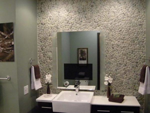 Декорированная камнем галькой стена в ванной