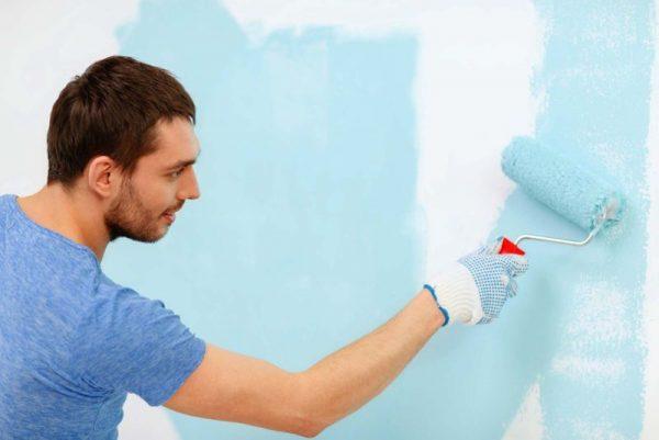 Нанесение голубой краски на стену