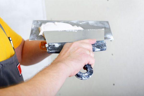 Нанесение шпаклевки на стену шпателем