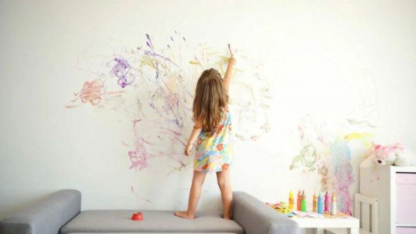 Девочка рисует акриловыми красками на стене