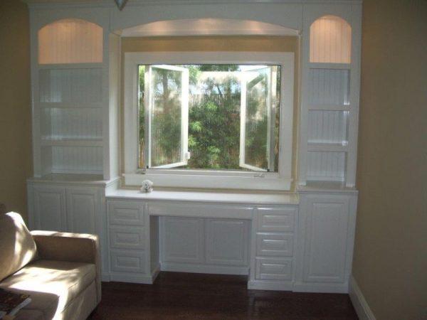Стол и шкаф вокруг окна в комнате
