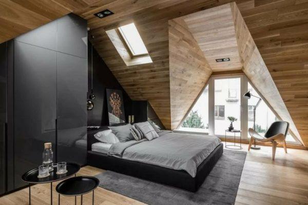 Интерьер спальни с мансардной крышей обшитой вагонкой