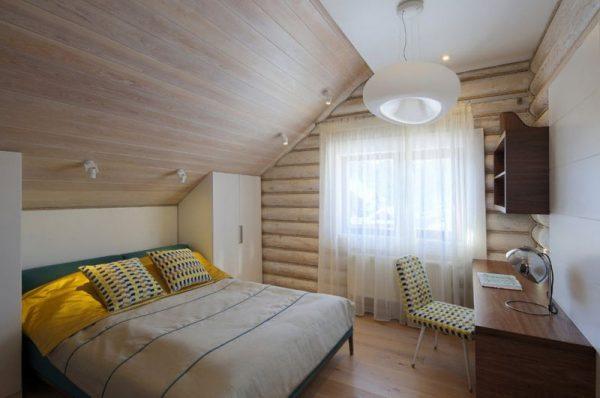 Спальня на мансарде в деревянном доме с потолком обшитым вагонкой