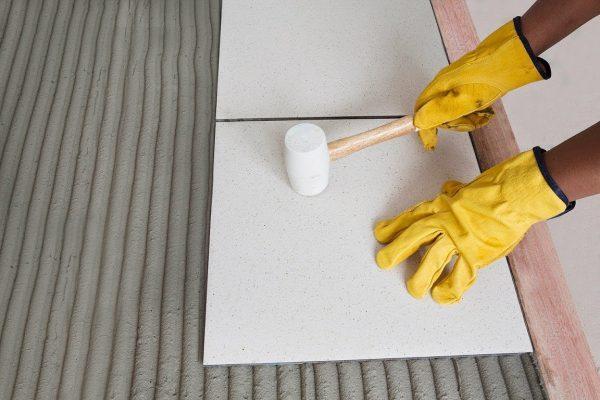 Выравнивание плитки резиновым молотком