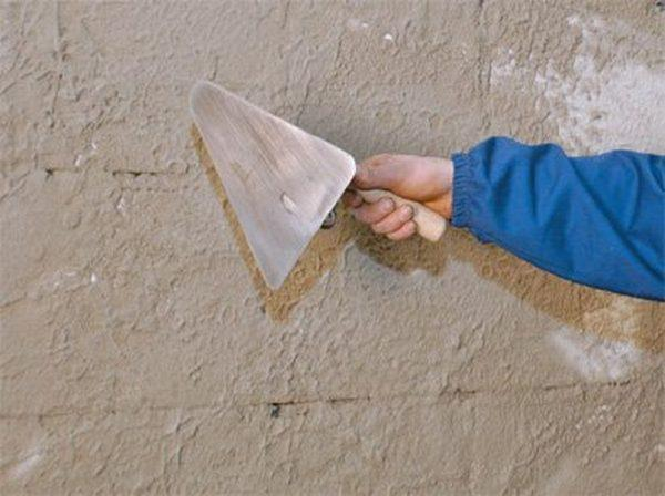 Нанесение цемента на забор мастерком