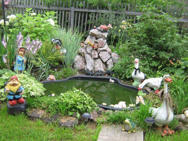 Фигурки вокруг водоема в саду