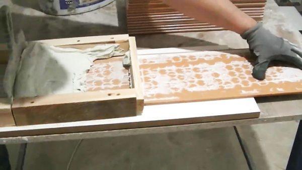 Плитку проталкивают через приспособление с клеем